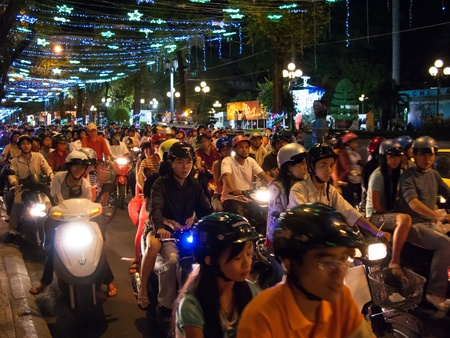 Ho Chi Minh City, Vietnam - January 18, 2008: Unidentified men and women drive their motorcycles during the Tet Lunar New Year celebrations. Tet is the most important and popular holiday and festival in Vietnam.