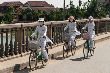 Hoi An, Vietnam - January 8, 2008: Three unidentified girls in traditional clothes ride their bicycles on a bridge. Hoi An, declared an UNESCO World Heritage site, is a major touristic destination in Central Vietnam.
