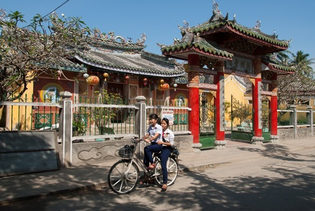 Hoi An, Vietnam - January 10, 2008: Two unidentified girls ride their bicycle in front of a buddhistic temple. Hoi An, declared an UNESCO World Heritage site, is a major touristic destination in Central Vietnam. Editorial