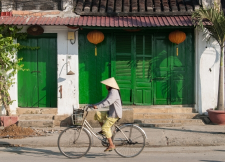 Hoi An, Vietnam - January 10, 2008: An unidentified woman rides her bicycle in front of a closed store with green doors. Hoi An, declared an UNESCO World Heritage site, is a major touristic destination in Central Vietnam.