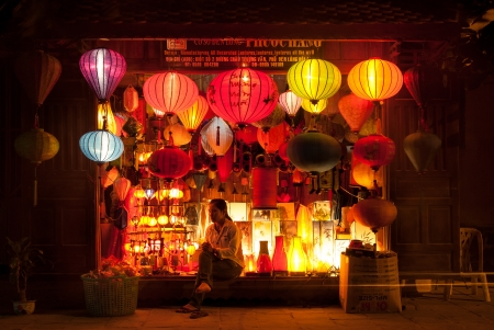 Hoi An, Vietnam - January 9, 2008: An unidentified woman sells colorful traditional lanterns in her store. Hoi An, an UNESCO World Heritage site, is a major touristic destination in Central Vietnam. Редакционное