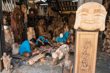 Hoi An, Vietnam - January 8, 2008: Four unidentified boys make wood-carven statues of Buddha in a workshop. Hoi An, an UNESCO World Heritage site, is a major touristic destination in Central Vietnam. Редакционное