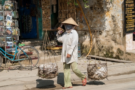 Hoi An, Vietnam - January 8, 2008: An unidentified woman carries vegetables for sale in traditional baskets. Street vending by bicycle, bike or on foot is an essential part of city life in Vietnam.
