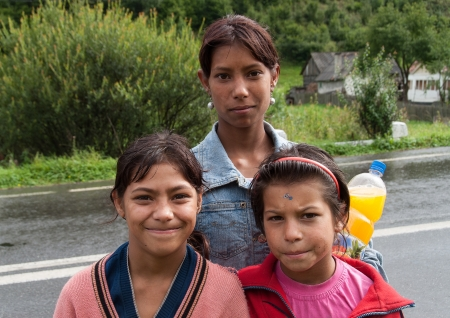 Transylvania, Romania - August 10, 2008: Three unidentified gypsy girls pose in the middle of the street. The Roma constitute one of the largest minorities in Romania.