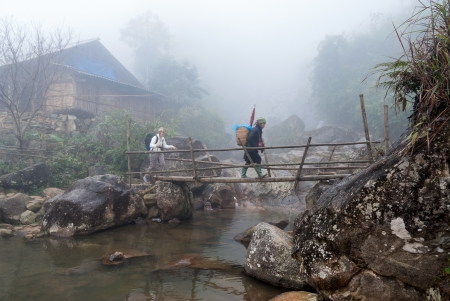 An unidentified tourist and her guide hike in the mist on January 18, 2008 in Sapa District, Vietnam. Sapa, a popular destination for tourists, is home to a great diversity of ethnic minorities.