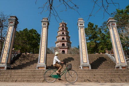 An unidentified woman rides her bicycle in front of the Thien Mu Pagoda on January 12, 2008 in Hue, Vietnam. Although seriously damaged during the war, its historic monuments earned the city a place in UNESCOs World Heritage Sites. Editorial