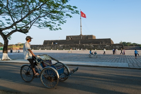 An unidentified cyclo driver waits for tourists in front of the Citadel on January 10, 2008 in Hue, Vietnam.  Although seriously damaged during the war, its historic monuments earned the city a place in UNESCO Редакционное