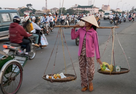 An unidentified woman carries vegetables for sale in traditional baskets on January 11, 2008 in Hue, Vietnam. Street vending by bicycle, bike or on foot is an essential part of city life in Vietnam.