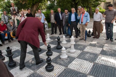 A group of unidentified men watch a game of chess in a park on June 26, 2009 in Sarajevo, Bosnia and Herzegovina