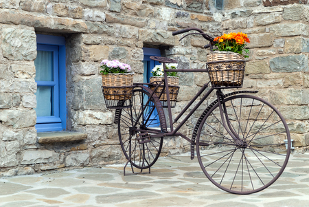 Old rusty bicycle with flowers in front of a traditional house in Epirus, Greece Stock Photo