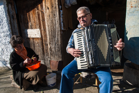 An unidentified old man plays his accordion, while his wife prepares lunch in a village near the Prespes Lakes on December 6, 2009  The Prespes Lakes are an important Transnational Park, divided between Albania, Greece and FYROM