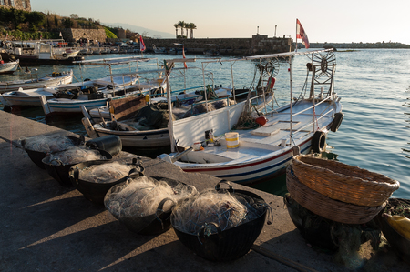 Fishing nets and boats at the harbor of Byblos, Lebanon, at sunset Stock Photo