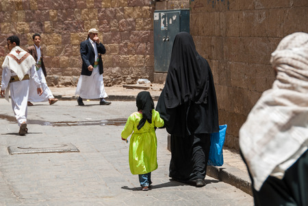 socially: An unidentified woman and her daughter in traditional dresses walk hand in hand in the local market on May 4, 2007 in Sanaa, Yemen. Although infant mortality is high, children in Yemen are culturally, socially and religiously valued.
