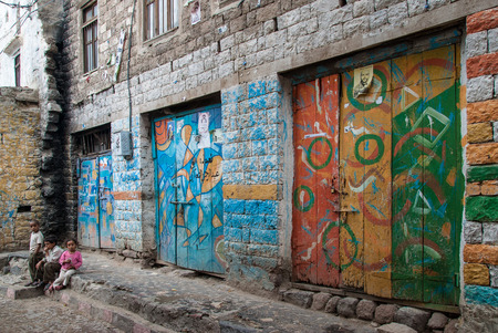 mortality: Three unidentified children play in front of a building decorated with graffiti on May 10, 2007 in Ibb, Yemen. Although infant mortality is high, children in Yemen are culturally, socially and religiously valued.
