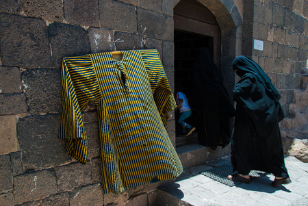 burqa: Two unidentified women dressed in black and a child enter a stone building on May 5, 2007, in Kawkaban, Yemen. Women do not hold many economic, social or cultural rights in Yemen, which is one of the poorest and most conservative countries in the Arab Wor Editorial