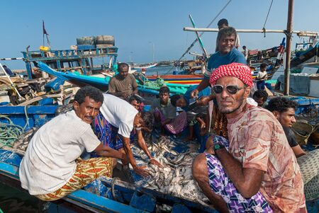 Unidentified fishermen in a boat prepare fish for sale in the famous fish market of the city on May 12, 2007 in Al Hudaydah, Yemen. Due to the rich with fish species Red Sea, fish markets play a central role in the economic life of Yemen.