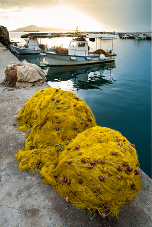 yellow boats: Yellow fishing nets and traditional fishing boats in a Greek island