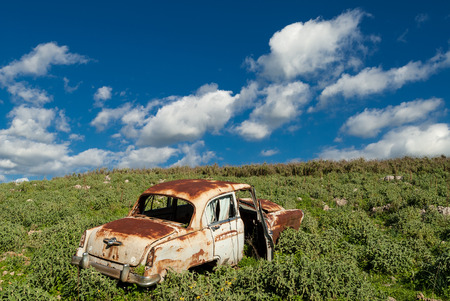 rusty car: Rusty car, abandoned in a field in Greece Stock Photo
