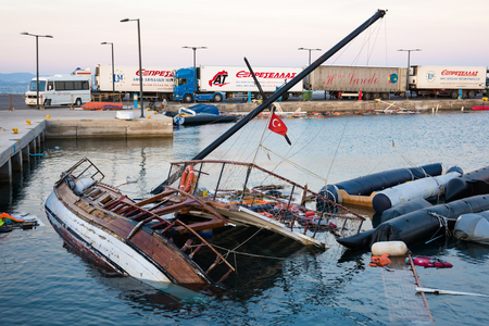 Half sunken ship and damaged boats on October 14, 2015 in the harbor of Kos island, Greece. Thousands of Syrian refugees passed from Turkey to Greek islands during  the summer of 2015.