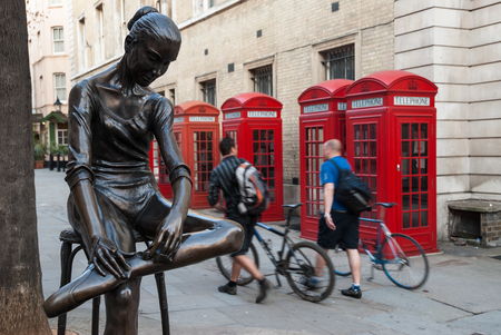 Two unidentified men with their bicycles walk in a street, passing by four red telephone boxes and a metallic statue of a dancer on April 8, 2007 in Covent Garden, London, UK. The red telephone box, designed in 1924, is along with the red post box and the