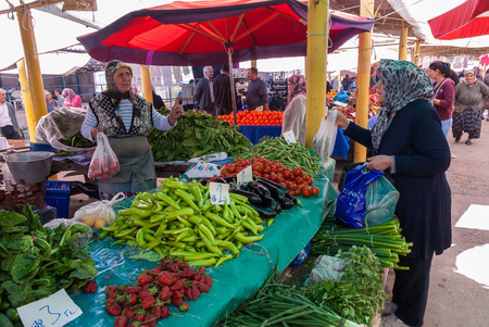 A woman with traditional clothes buys vegetables in the open market of the city on April 25, 2014 in Ayvacik, Turkey. Open markets in Turkey is a popular old tradition that comes from the Ottoman times. Editorial