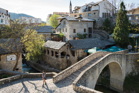 neretva: A young woman walks near an old bridge on April 15, 2015 in Mostar, Bosnia and Herzegovina. Almost completely destroyed in 1993 during the Croat-Bosniak War, todays Mostar is a very popular place among tourists.