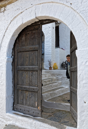 traditional climbing: A boy looks through the half open traditional wooden door of his house on April 12, 2015 in Berat, Albania. Inscribed on the UNESCO World Heritage List, the old town of Berat is a striking collection of white Ottoman houses, climbing up the hill to its ca Editorial