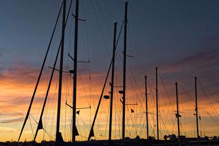 Silhouettes of masts at sunset in the harbor of Kos, Greece Stock Photo