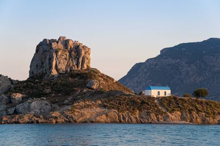 kos: Landscape with islet and traditional church at sunset in Kos island, Greece