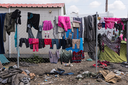 immigrants: Refugees and immigrants try to dry their clothes after heavy rain on March 17, 2015 in the refugees camp of Eidomeni, Greece. For several weeks, more than 10.000 refugees and immigrants wait here for the borders to open.