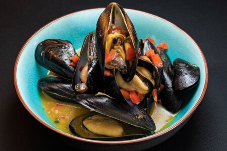 Delicious steamed mussels in turquoise plate