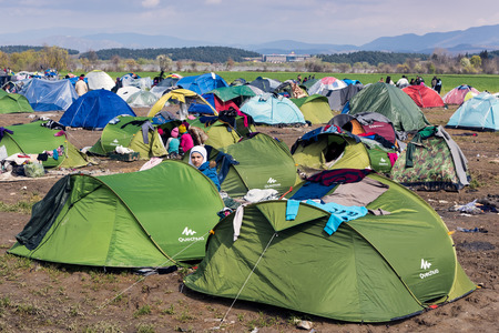 immigrants: Refugees from Syria sit by their tents on March 17, 2015 in the refugee camp of Idomeni, Greece. For several weeks, more than 10.000 refugees and immigrants wait here for the borders to open.