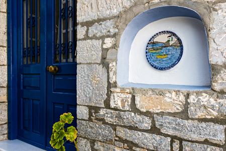 Entrance of traditional stone house, decorated with painted plate, in the village of Trikeri, Thessaly, Greece Stock Photo