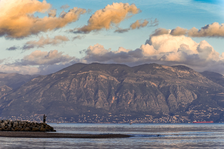 Man fishing at sunset with a distant view of Mt Taygetos in Peloponnese, Greece