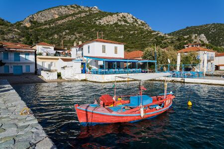 Red fishing boat and white houses at the village of Agia Kyriaki in Thessaly, Greece
