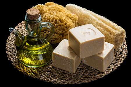 Handmade olive oil soaps together with two sea sponges and an oil bottle