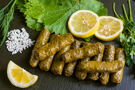 Delicious stuffed grape leaves (the traditional dolma of the mediterranean cuisine) on black dish with leaves, lemon slices, rice, parsley and dill Stock Photo