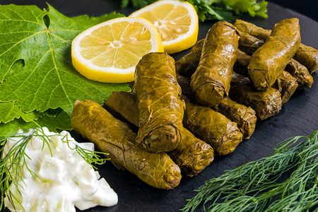 Delicious stuffed grape leaves (the traditional dolma of the mediterranean cuisine) on black dish with leaves, lemon slices, dill and tzatziki sauce Stock Photo