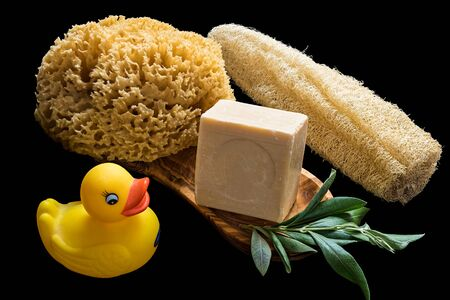 Handmade olive oil soaps together with two sea sponges, a duck toy and a branch of olive tree on black background
