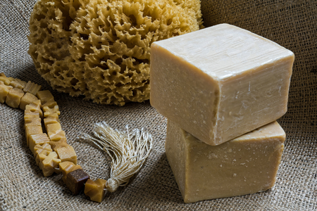 Handmade olive oil soaps together with a natural sea sponge and a string of beads made of soap on sack cloth