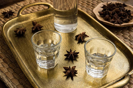matting: Glasses of traditional drink Ouzo or Raki on bronze dish with anise star seeds Stock Photo