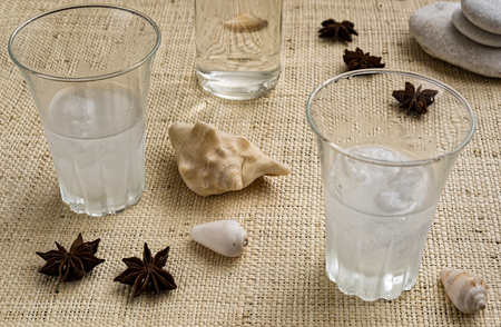 Glasses of traditional drink Ouzo or Raki on natural matting with anise star seeds and shells Stock Photo