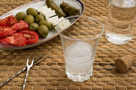 Glass of traditional drink Ouzo or Raki and appetizers on natural matting