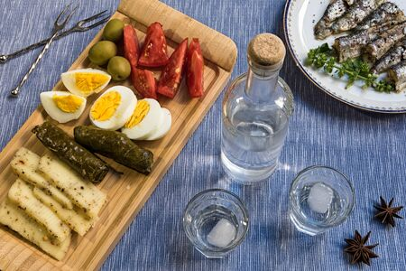 Glasses and bottle of traditional drink Ouzo or Raki and appetizers Stock Photo - 84549584