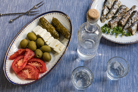 Two glasses and bottle of traditional drink Ouzo or Raki and appetizers on blue matting Stock Photo - 85850703
