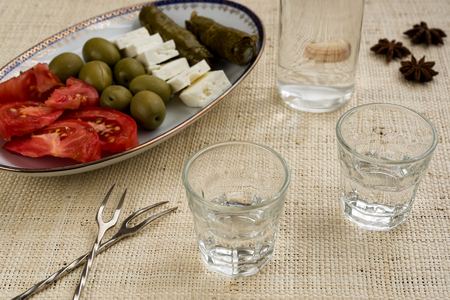 Two glasses and bottle of traditional drink Ouzo or Raki and appetizers on natural matting