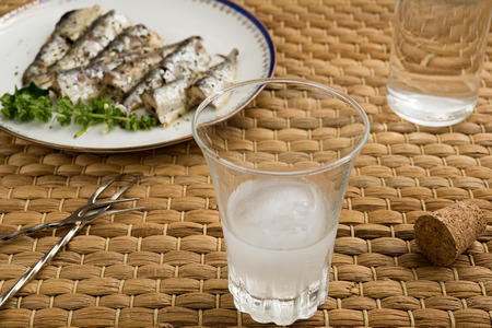 Glass and bottle of traditional drink Ouzo or Raki and appetizers on natural matting Stock Photo