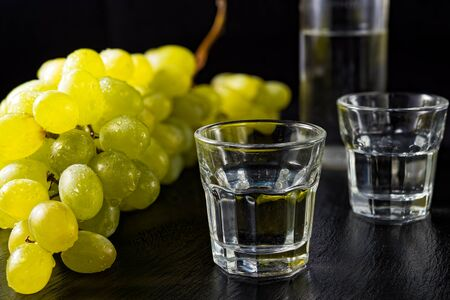 Two glasses and bottle of traditional drink Ouzo or Raki on black dish with a branch of grapes Stock Photo - 86433434