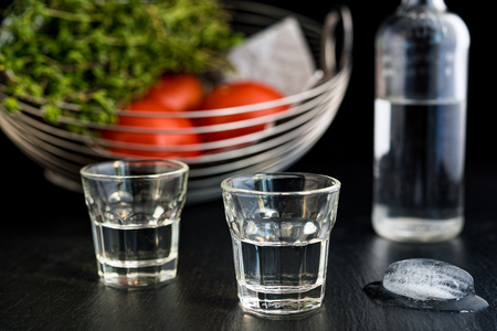 Two glasses and bottle of traditional drink Ouzo or Raki on black dish Stock Photo