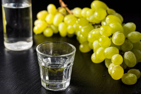 Glasses and  bottle of traditional drink Ouzo or Raki on black dish with a branch of grapes Stock Photo - 86373422